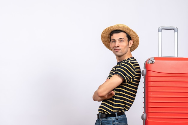 赤いスーツケースの近くに立っている手を交差する麦わら帽子を持つ正面図の若い男