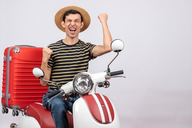 Vista frontale del giovane con cappello di paglia sul ciclomotore che esprime la sua felicità
