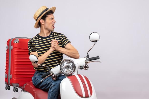 Vista frontale del giovane con cappello di paglia sul ciclomotore che tengono le mani insieme