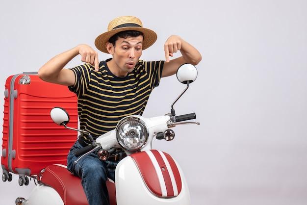 Vista frontale del giovane con cappello di paglia sul ciclomotore che punta le dita di seguito