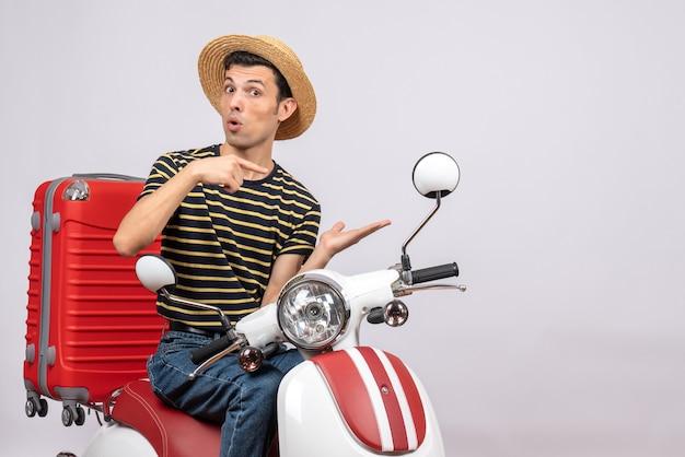 Vista frontale del giovane con cappello di paglia sul ciclomotore che punta alla sua mano