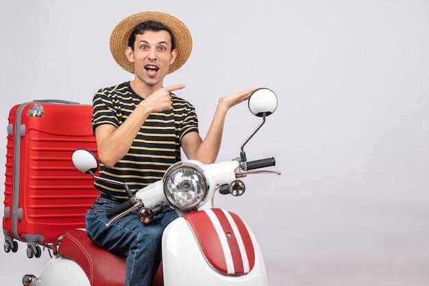 Vista frontale del giovane con cappello di paglia sul ciclomotore che punta a qualcosa