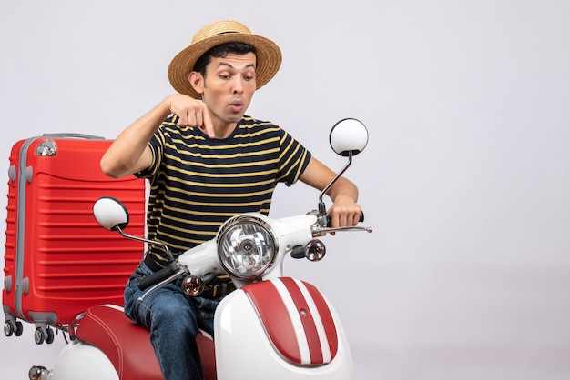 Front view of young man with straw hat on moped pointing with fingers below