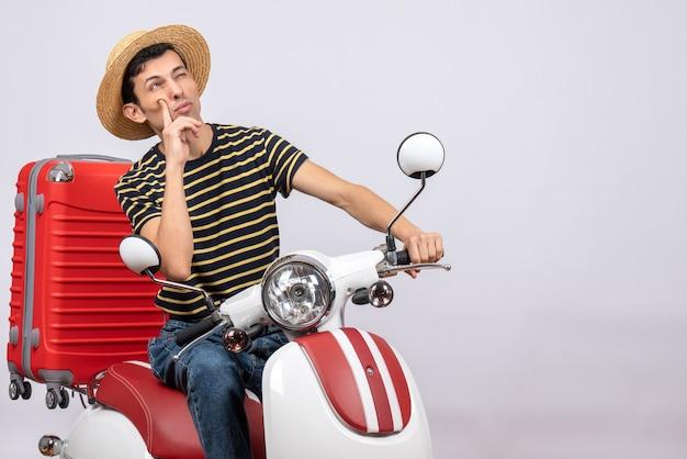 Giovane vista frontale con cappello di paglia sul ciclomotore pensando a qualcosa