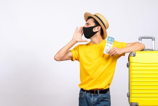 誰かを呼び出す旅行チケットを保持している黄色のスーツケースの近くに立っている麦わら帽子を持つ正面図の若い男