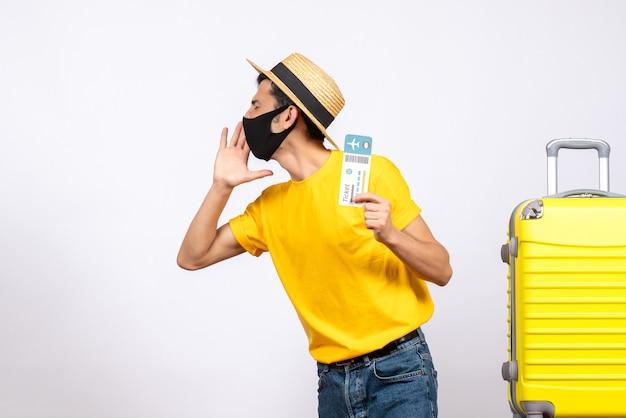 何かを呼び出す旅行チケットを保持している黄色のスーツケースの近くに立っている麦わら帽子を持つ正面図の若い男