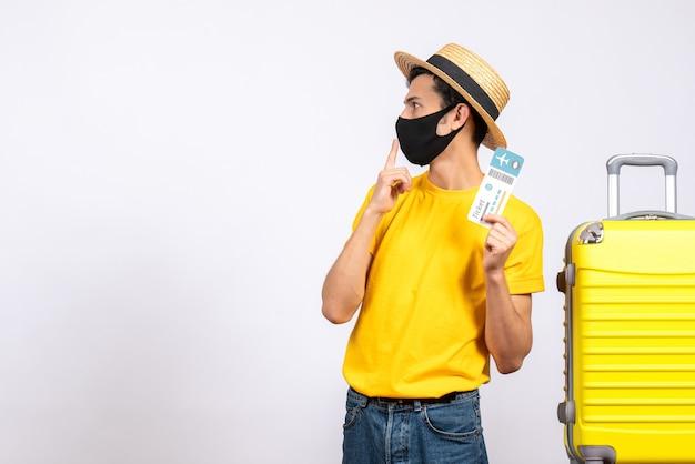 何かを見ている旅行チケットを保持している黄色のスーツケースの近くに立っている麦わら帽子の正面図
