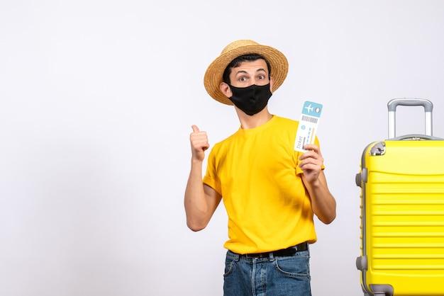 後ろを指す旅行チケットを保持している黄色のスーツケースの近くに立っている麦わら帽子を持つ正面図の若い男