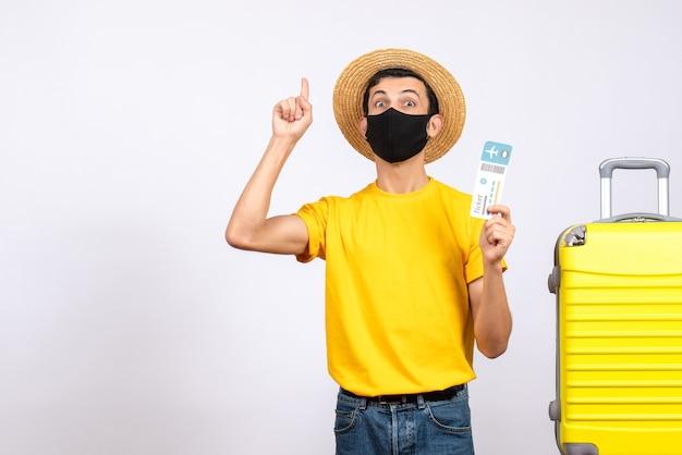손가락을 가리키는 여행 티켓을 들고 노란색 가방 근처에 서 밀짚 모자와 전면보기 젊은 남자