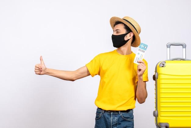 Вид спереди молодой человек в соломенной шляпе, стоящий возле желтого чемодана с проездным билетом, указывая большим пальцем вверх знак