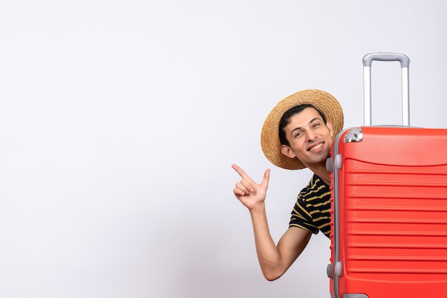 Giovane di vista frontale con il cappello di paglia che sta dietro la valigia rossa che indica qualcosa