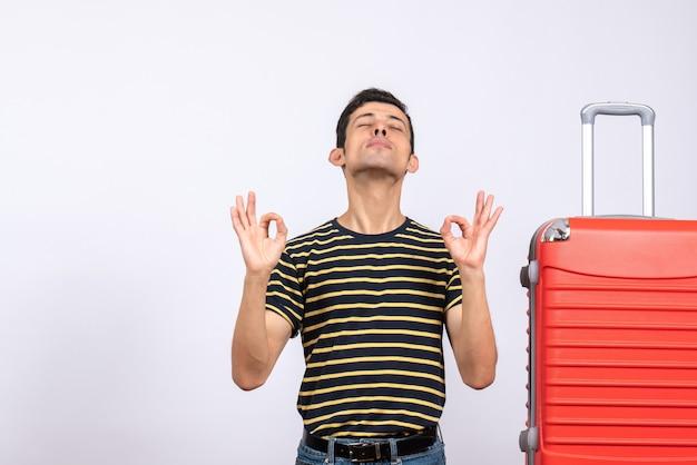 縞模様のtシャツと赤いスーツケースを持った正面図の若い男が目を閉じてokサインを作る