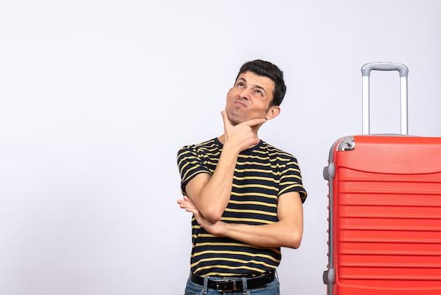 何かを考えている縞模様のtシャツと赤いスーツケースを持つ正面図の若い男