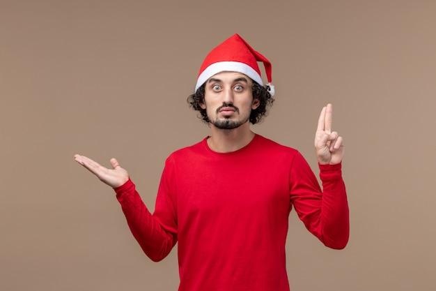 Вид спереди молодой человек с удивленным выражением лица на коричневом столе, праздничные эмоции, рождество