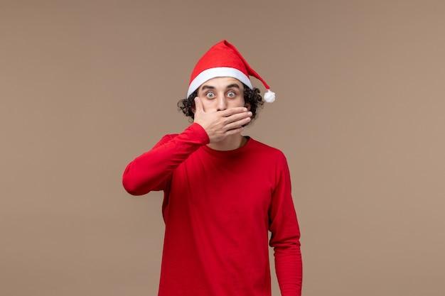 Вид спереди молодой человек с удивленным лицом на коричневом фоне рождественские эмоции праздник