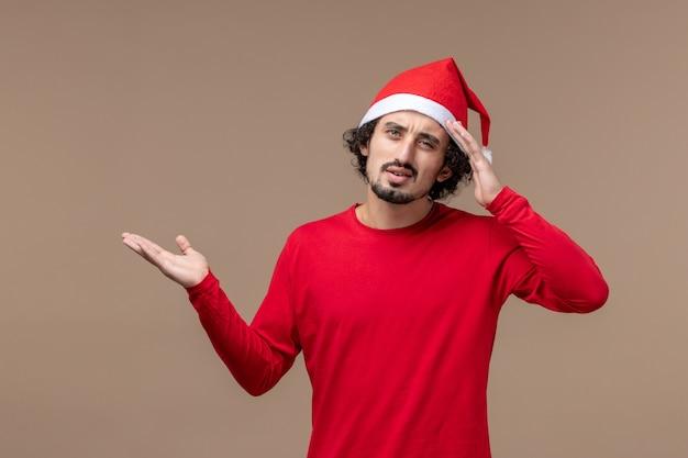 Вид спереди молодой человек с выражением мышления на коричневом фоне, праздничные эмоции, рождество