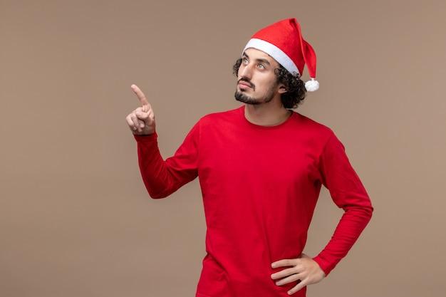 Вид спереди молодой человек с думающим лицом на коричневом фоне праздник рождественские эмоции