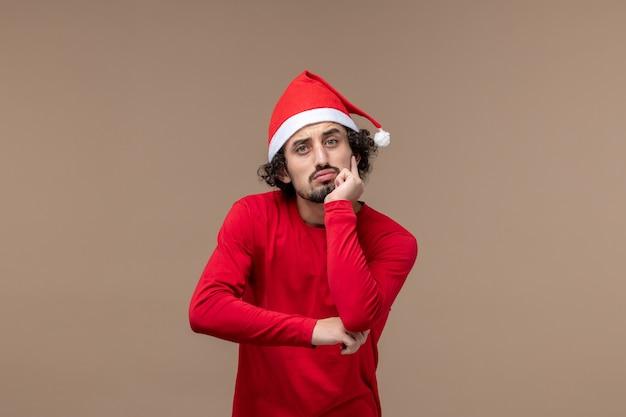 Вид спереди молодой человек с думающим лицом на коричневом столе, рождественский праздник эмоций
