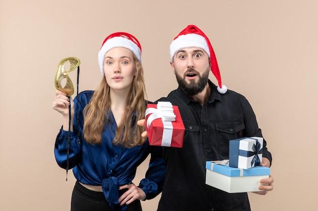 Vista frontale del giovane con la donna che tiene i regali sulla parete rosa