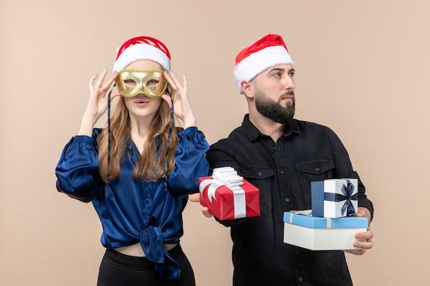 Vista frontale del giovane con la donna che tiene i regali e indossa la maschera sulla parete rosa