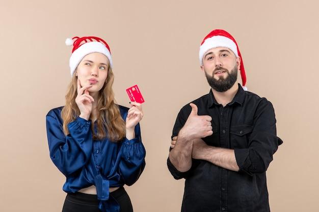 Vista frontale del giovane con la donna che tiene una carta di credito sul muro rosa