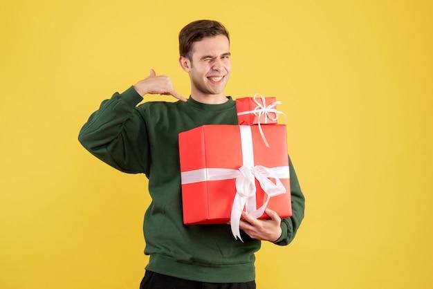 Вид спереди молодой человек с рождественским подарком делает звонок мне телефонный знак, стоящий на желтом фоне