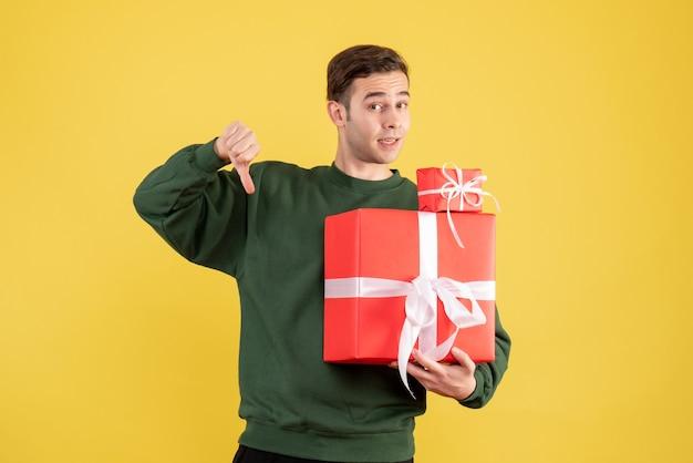Вид спереди молодой человек с рождественским подарком, делая большой палец вниз знак, стоящий на желтом фоне