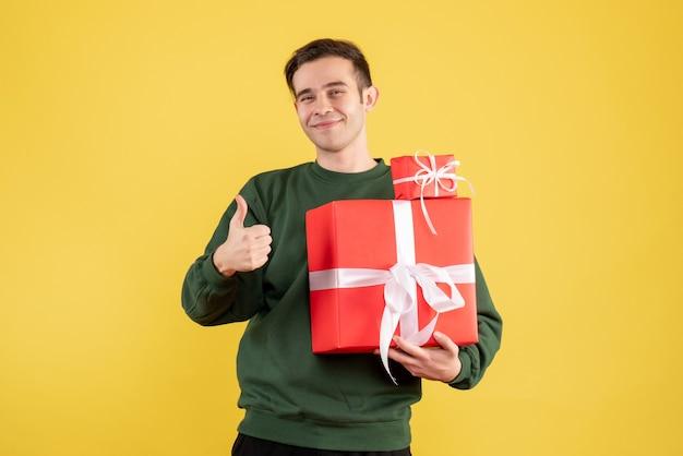 Вид спереди молодой человек с рождественским подарком, делая большой палец вверх знак, стоящий на желтом фоне