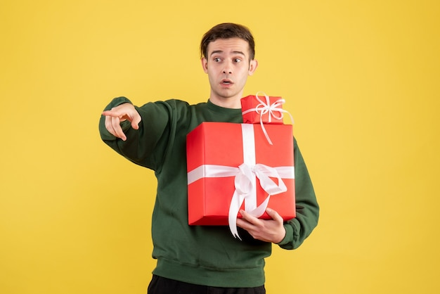 Front view young man with xmas gift pointing at something standing on yellow background