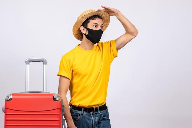 大きな驚きで何かを見ている黄色のtシャツと赤いスーツケースを持つ正面図の若い男