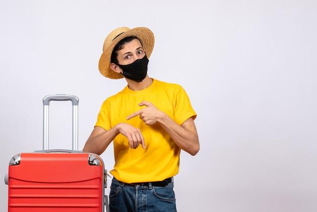 Giovane di vista frontale con la maglietta gialla e la valigia rossa che chiede tempo