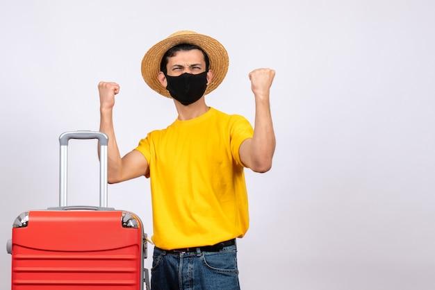 Giovane vista frontale con maglietta gialla e valigia rossa che esprime i suoi sentimenti
