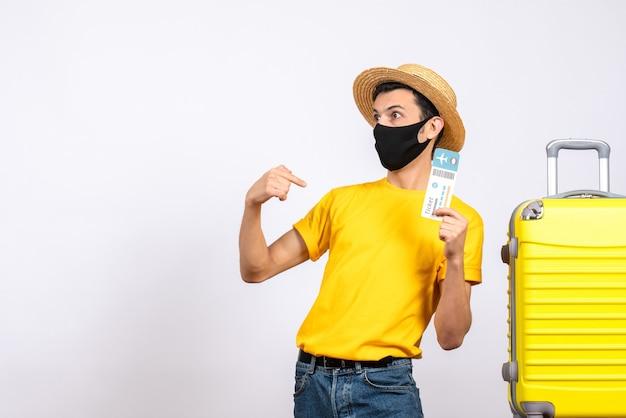 自分を指している旅行チケットを保持している黄色のスーツケースの近くに立っている黄色のtシャツを持つ正面図の若い男