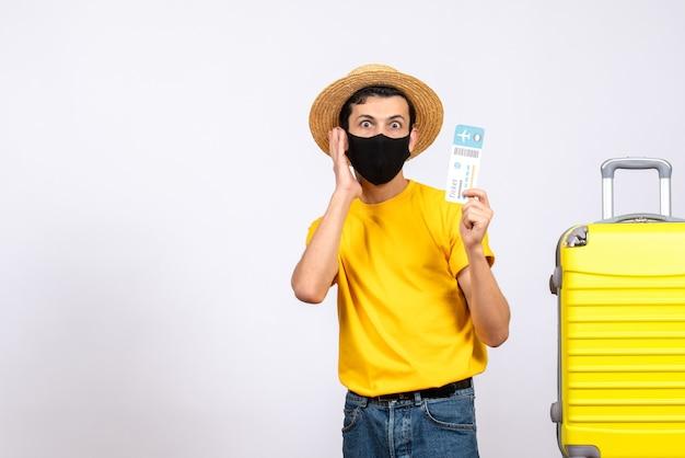 旅行チケットを保持している黄色のスーツケースの近くに立っている黄色のtシャツと正面図