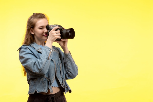A front view young modern woman in blue shirt black trousers and jean coat posing happy expression smiling holding photo camera taking photos