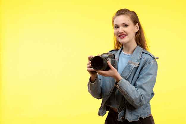 A front view young modern woman in blue shirt black trousers and jean coat posing happy expression smiling holding photo camera