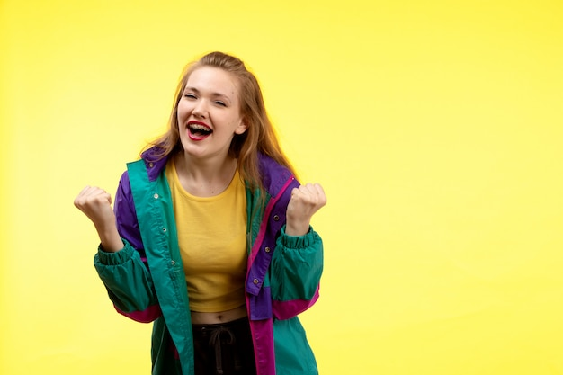 A front view young modern woman in yellow shirt black trousers and colorful jacket posing happy expression
