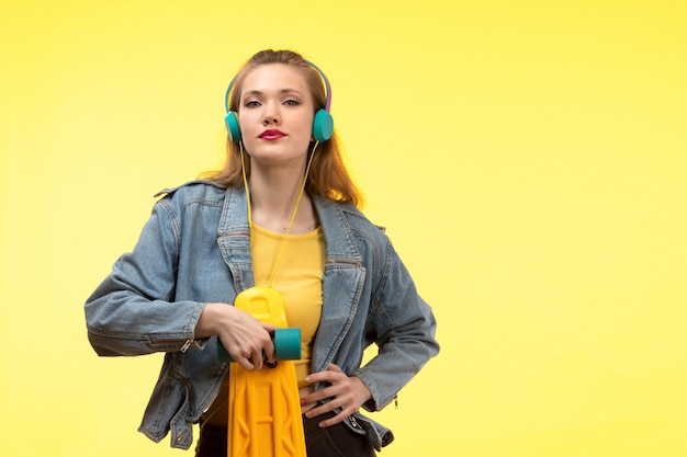 A front view young modern woman in yellow shirt black trousers and jean coat holding skateboard with colored earphones