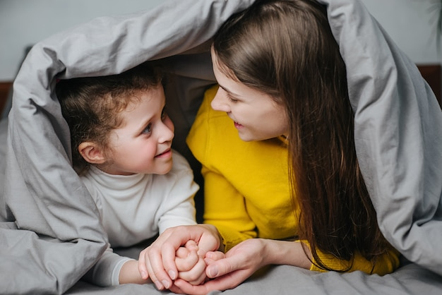 Front view of young mother and little girl enjoying sweet moments of parent and kid bonding together at cozy home. happy loving mom talking with his cute child daughter lying in bed covered blanket
