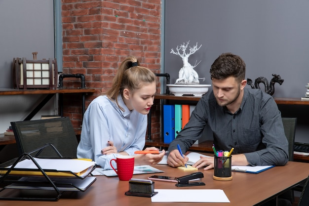 Vista frontale del giovane team d'ufficio motivato e laborioso focalizzato su un problema nell'ambiente d'ufficio