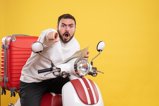 Front view of young nervous man sitting on motorcycle with suitcase on it holding map pointing forward on isolated yellow background