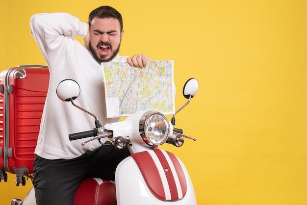 Vista frontale di un giovane uomo nervoso e turbato seduto su una motocicletta con la valigia sopra con in mano una mappa che soffre di dolore all'orecchio su sfondo giallo isolato