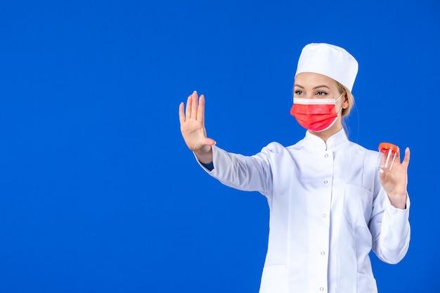 Вид спереди молодая медсестра в медицинском костюме с маской, держащая флягу на синем фоне, пандемия коронавируса, больничная медицина, врач, лекарства, вирусная вакцина