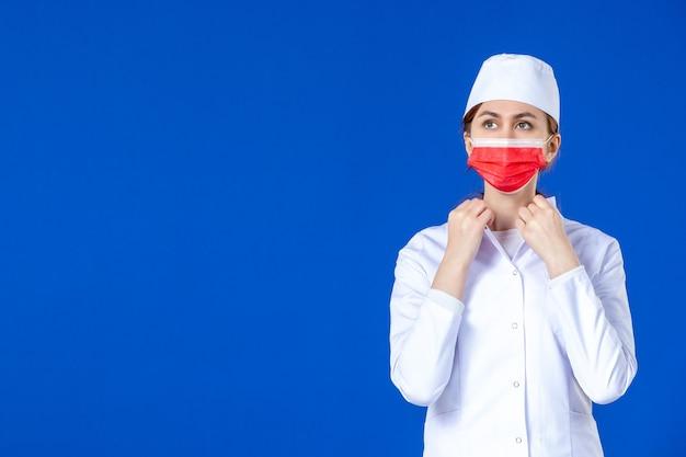 파란색 벽에 빨간 마스크와 의료 소송에서 전면보기 젊은 간호사
