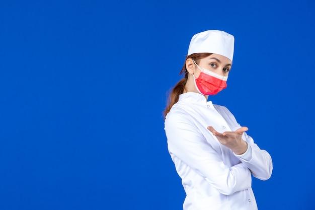 Вид спереди молодая медсестра в медицинском костюме с красной маской на синей стене