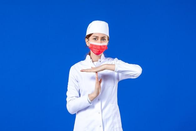 Вид спереди молодая медсестра в медицинском костюме с красной защитной маской на синей стене