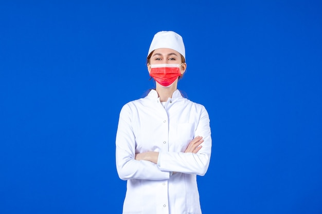 青い壁に赤い保護マスクと医療スーツの正面図若い看護師
