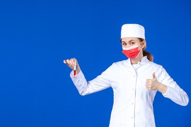 Вид спереди молодая медсестра в белом медицинском костюме с красной маской и инъекцией в руках на синей стене