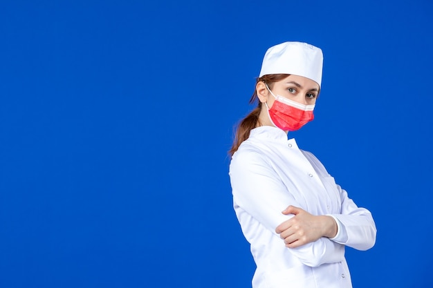 Front view young nurse in medical suit with red mask on blue wall