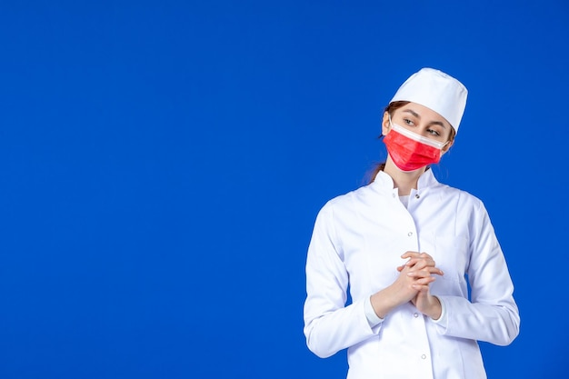 Front view of young nurse in medical suit with red mask blue